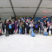 Na zdjęciu grupowym dzieci ustawione na tafli lodowiska w towarzystwie mikołaja stojącego za nimi