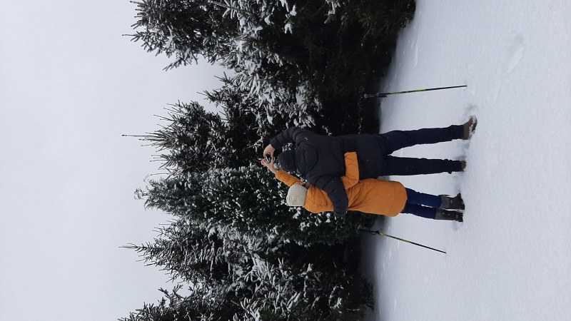 Na zdjęciu para stojąca na śniegu z kijkami wykonująca znak serduszka