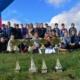 Na zdjęciu grupa uczniów ustawiona do zdjęcia pod bramą startową a przed nimi zdobyte w zawodach puchary