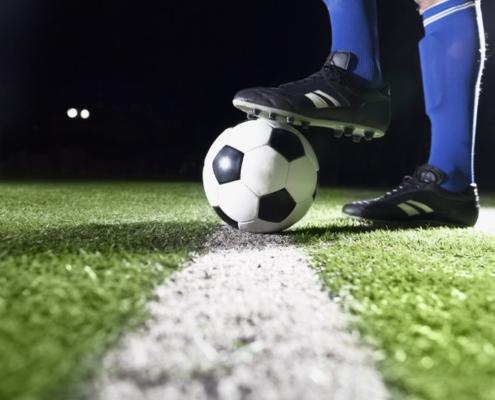 Na zdjęciu nogi piłkarza przytrzymujące piłkę nożną na murawie boiska