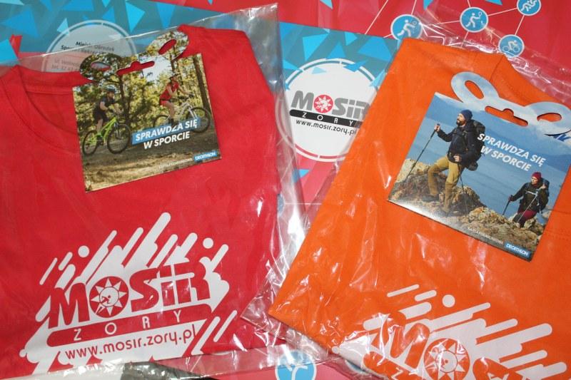 Na zdjęciu czerwone i pomarańczowe koszulki MOSiR i dwa bony do sklepu Decathlon