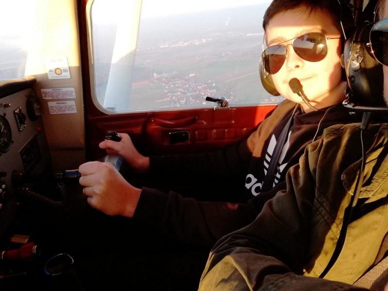 Na zdjęciu Franek Krakowczyk siedzący za sterami samolotu, w okularach przeciwsłonecznych i słuchawkach