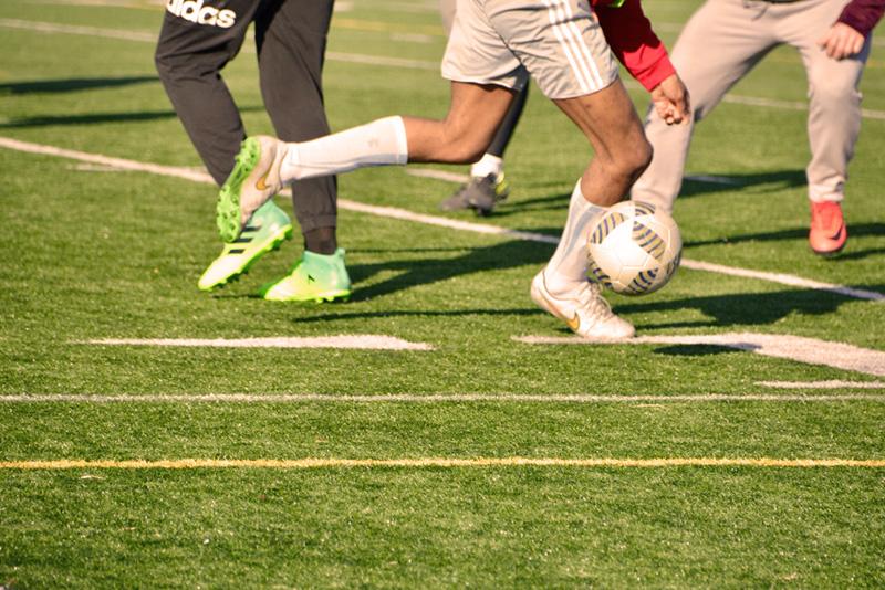 Na zdjęciu trzech piłkarzy grających w piłkę nożną na zielonej murawie, widoczne tylko nogi