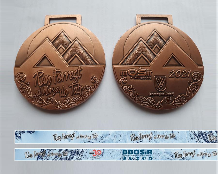 Na zdjęciu projekt medalu z logo imprezy oraz dwie niebieskie wstążki do medalu, w tle góry