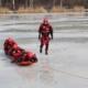 Na zdjęciu grupa strażaków ćwiczy wyciąganie z wody topielca na zamarzniętym Śmieszku
