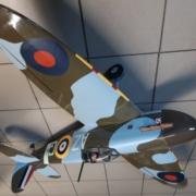 Na zdjęciu model samolotu Spitfire w kolorze moro khaki-niebieski stojący na podłodze
