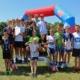 Na zdjęciu biegacze w ustawieniu grupowym z dyplomami na podium w parku cegielnia