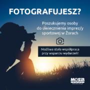 Na zdjęciu informacja o poszukiwanej osobie do fotografii, w tle sylwetka fotografa robiącego zdjęcie w terenie
