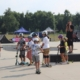 Na zdjęciu grupa dzieci z instruktorem na skate parku ćwicząca jazdę na hulajnodze