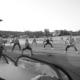 Na czarno-białym zdjęciu zajęcia fitness w parku cegielnia, w tle ćwiczący