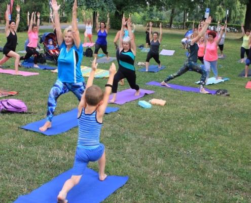 Na zdjęciu uczestnicy zajęć z jogi na trawie podczas ćwiczeń