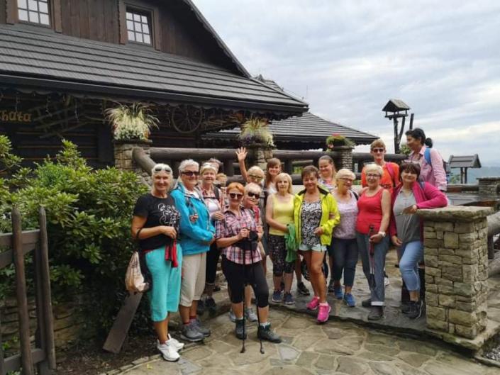 Na zdjęciu grupa wycieczkowiczów ustawiona do zdjęcia grupowego na tle domku w górach