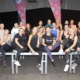 na zdjęciu grupa ćwiczących w zajęciach ustawiona do zdjęcia grupowego na podeście