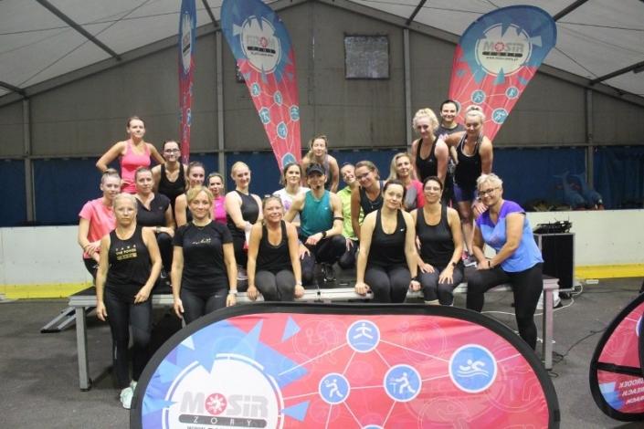 na zdjęciu grupa uczestniczek zajęć fitness z instruktorką w namiocie lodowiska ustawiona do zdjęcia