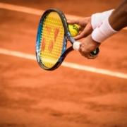 na zdjęciu ręce tenisisty na tle kortu tenisowego trzymające rakietę i piłkę