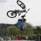 na zdjęciu zawodnik na rowerze wykonujący trick na skate parku