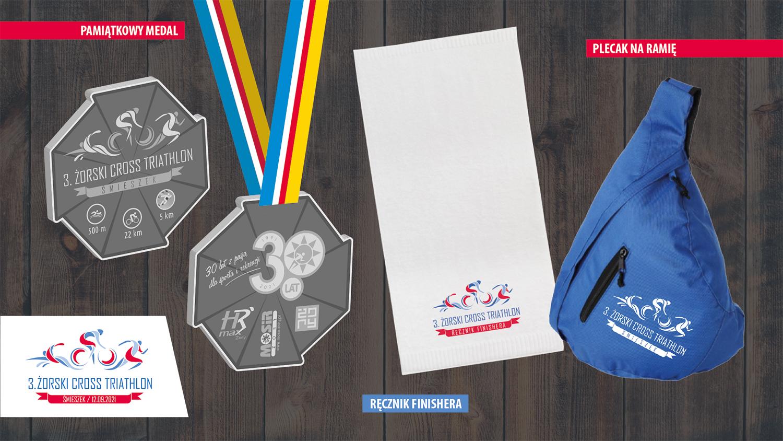 grafika prezentuje na ciemnym, drewnianym tle medal pamiątkowy, biały ręcznik i niebieski plecak na ramię