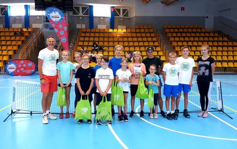 na zdjęciu grupa uczestników szkółki tenisa w zdjęciu grupowym w hali sportowej