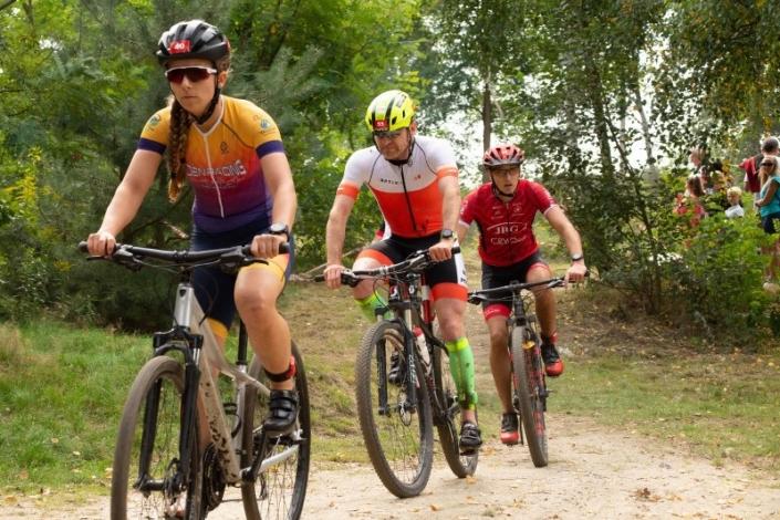 na zdjęciu trzech kolarzy podczas jazdy na trasie żorskiego cross triathlonu