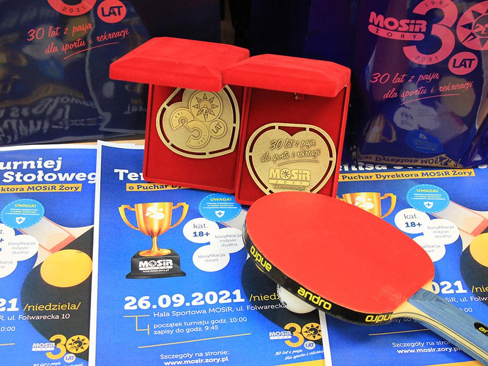 zdjęcie przedstawia pamiątkowe złote medale w czerwony etui, rakietkę, piłkę i plakaty turnieju tenisa
